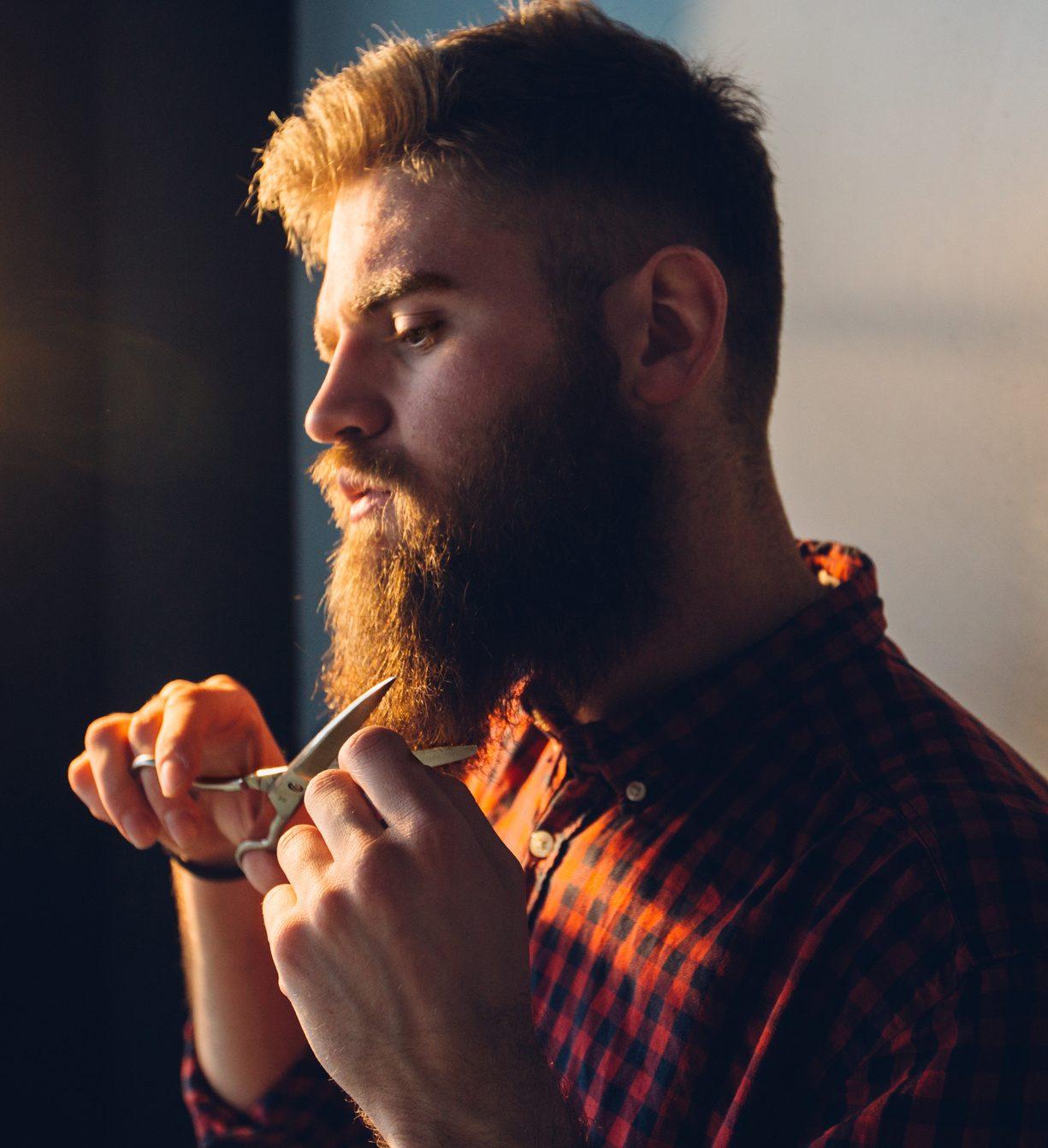 man cutting his beard with scissors